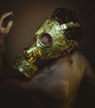 Protective, Man with gold gas mask and arabesques in poses of drowning and desperation, depression and psychiatry concept.