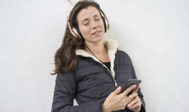 Lifestyle, Brown-haired woman listening to music with the mobile. enjoying music with golden and white helmets on the street in winter