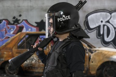 armed police with riot helmet and vest in a scene with a burnt car and riots