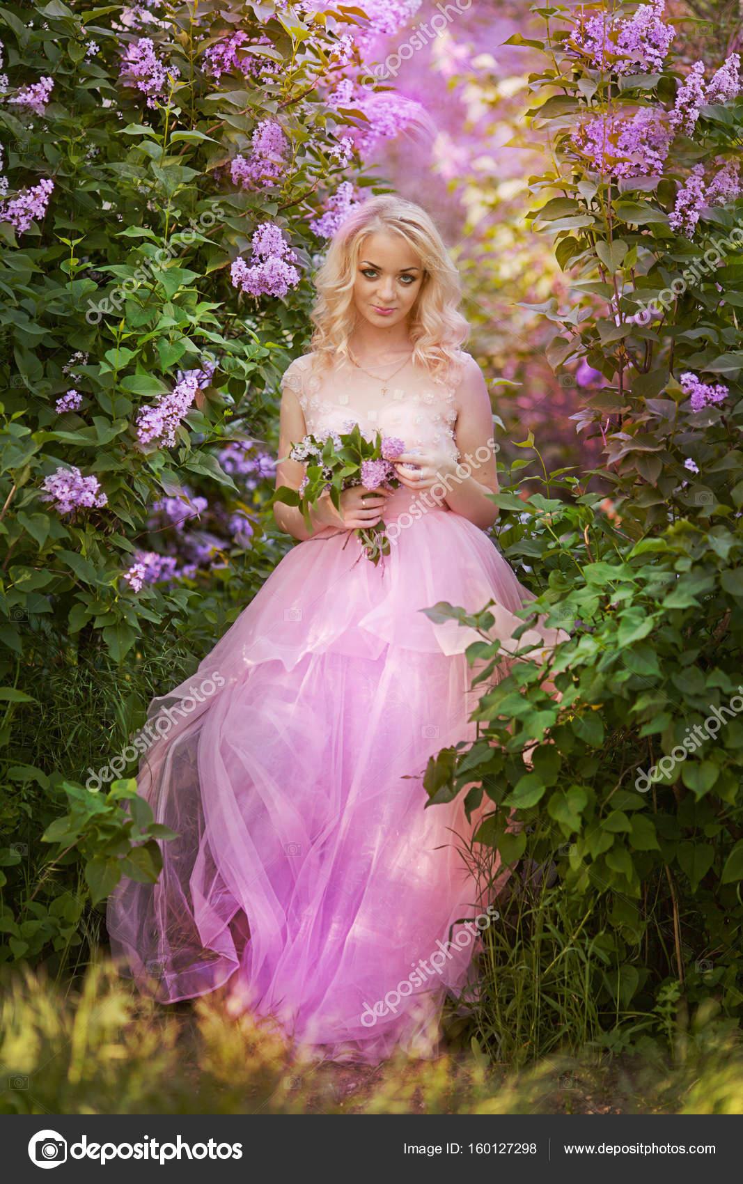 Hermosa mujer disfrutando jardín lila, joven mujer con flores en el ...