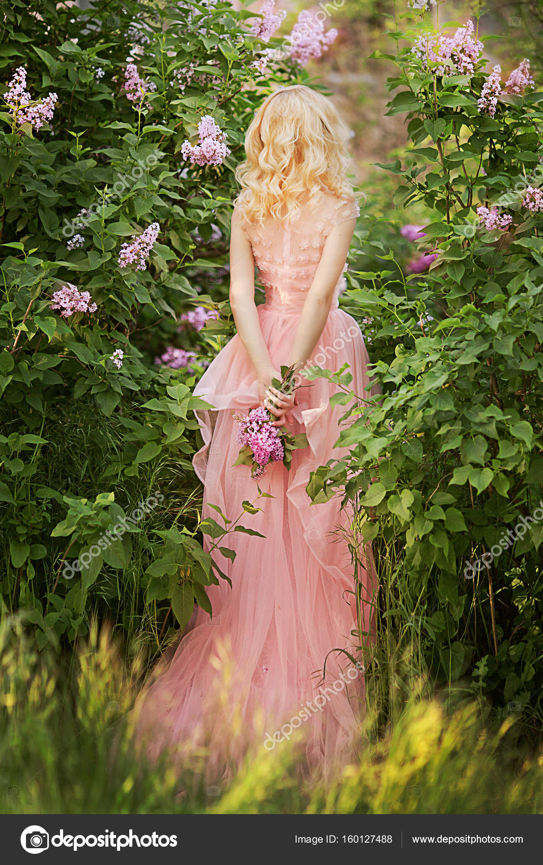 Beautiful woman enjoying lilac garden young woman with flowers in a girl in a lavender pink garden photo by olenakucher izmirmasajfo