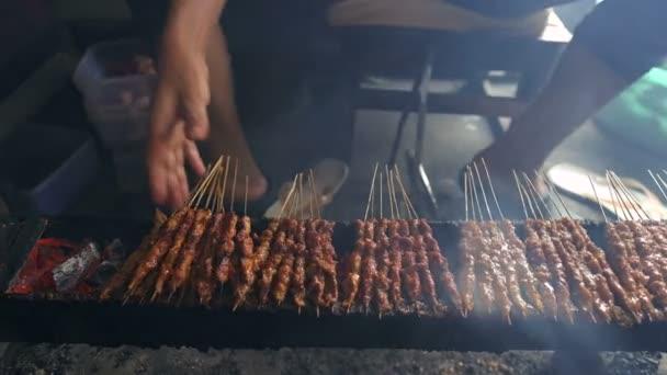 Restaurace s pouličním jídlem prodávající satay, grilované maso z dřevěného uhlí na špejlích. Lahodné
