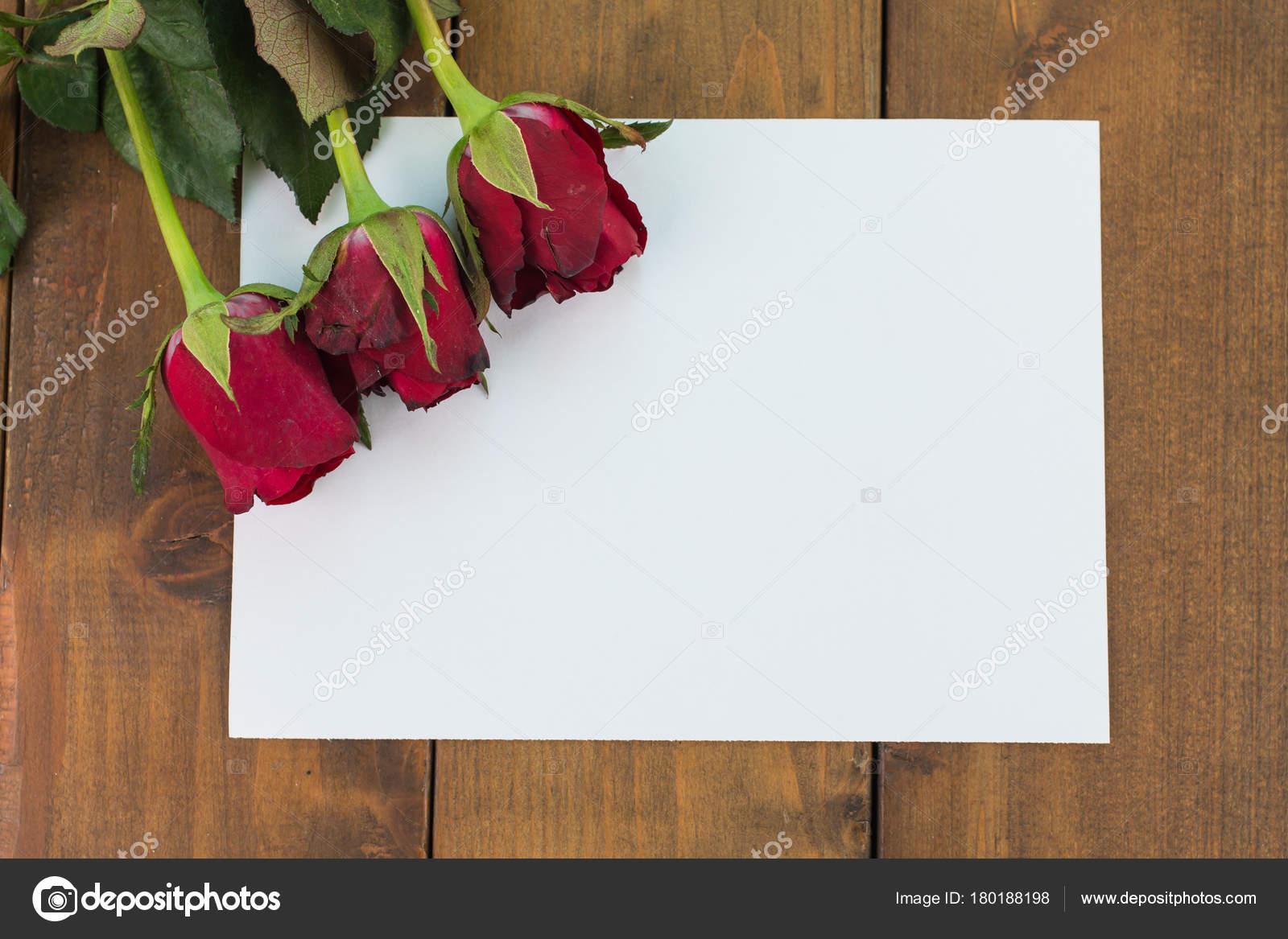 Close Up Of Red Roses On A Wooden Background With Blank Message Sign
