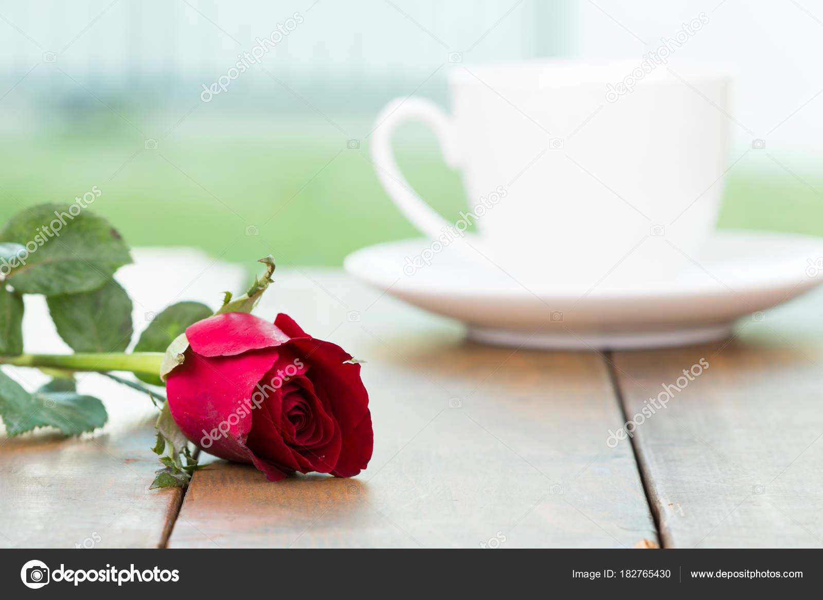 Mignon blanc petite tasse de café avec une fleur rose rouge sur la ...