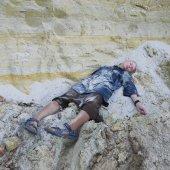 Mladá žena působí zabitých, padlých k smrti nebo spí poblíž stěny útesu
