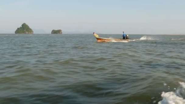 Fisherman in the traditional Thai longtail boat floats on the waves