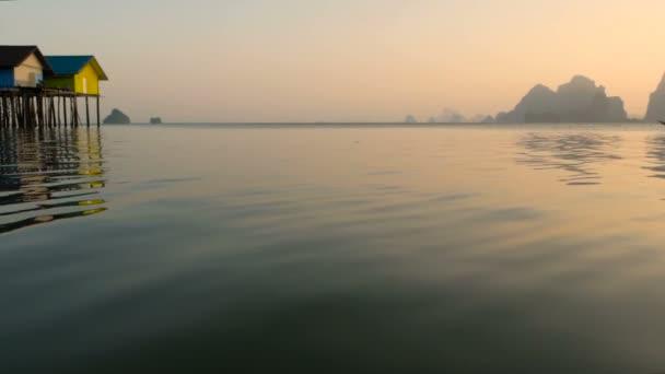 Rybářů domy povznést nad okraje waterss při západu slunce. Silueta lodi