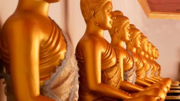 Egy sorban ült arany Buddha szobrok.