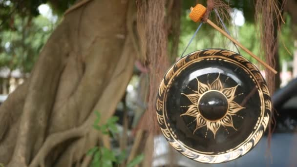 Small traditional gong hanging on background of old banyan tree in daylight. Symbol of buddhist religion. Tropical idyllic natural background. Zen meditation, retreat and enlightenment concept.