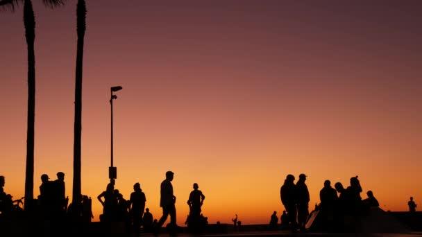 Silueta mladého skákajícího skateboardisty na dlouhém prkně, letní pozadí západu slunce. Venice Ocean Beach skatepark, Los Angeles California. Teenky na skateboardu, extrémní park. Skupina teenagerů.