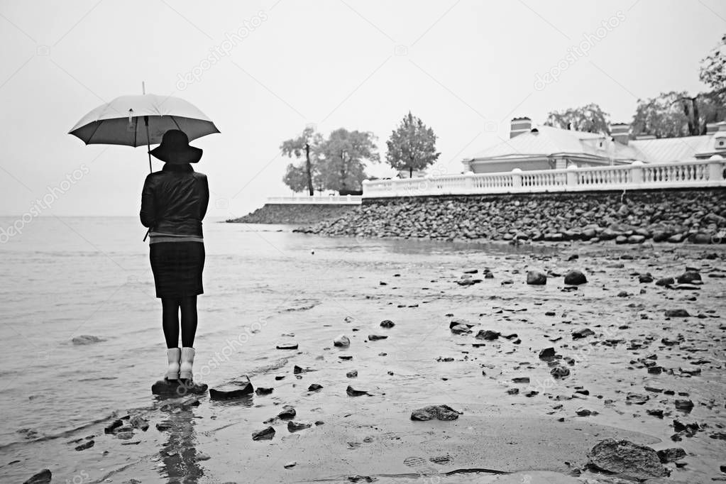 woman with an umbrella by the sea