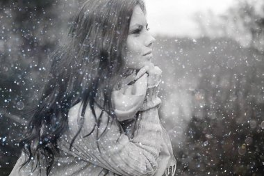 young girl with snowflakes in the air