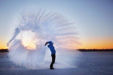 Man throwing snow at sunset