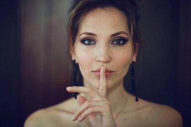 girl holding finger on mouth
