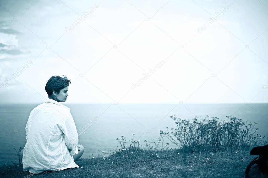 woman sitting at bank of river
