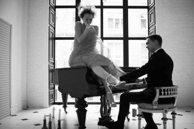 Man playing grand piano and woman