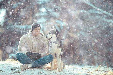 guy with a dog walks in the winter forest, sunny Christmas landscape, friends in nature in the park man and dog