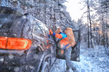 Hiking sport forest extreme winter, male traveler with a backpack next to a car in the forest view