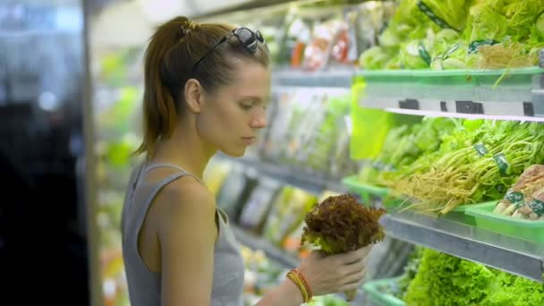 American vegan girl choosing fresh green salad standing in organic shop.