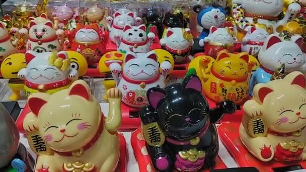 Hong Kong, Čína - srpen 2019: obchod se suvenýry. Tradiční maneki neko štěstí kočka figurky na displeji na trhu v jihovýchodní Asii