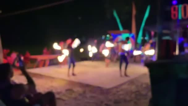 Asian artists showing fire show and dancing on dark night at exotic island.