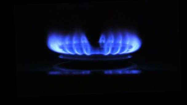 das Auftreten einer blauen Gasflamme. Gasherd auf schwarzem Hintergrund