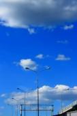 Stadtbild Straßenlaternenmasten auf spitz zulaufenden Stahlpfosten auf der Autobahn vor wolkenverhangenem Himmel.