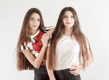 Family relationships, friendship concept. Two beautiful women sisters brunette with a long straight hair posing charmingly. Studio shot on a light gray background