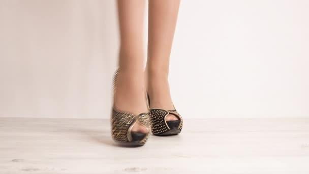 close-up záběry ženy ve stylové vysoké podpatky boty na bílém pozadí