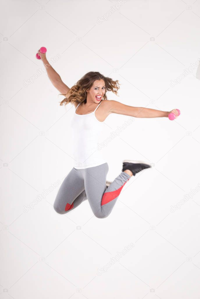 Fitness woman jumping in the air with dumbbells