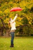 schöne Frau mit Regenschirm in einem Park