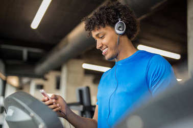 Handsome african american man working out at the gym while listening to music and smiling