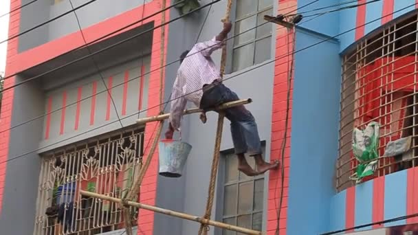 Worker on a dangerous bamboo scaffolding paints a building in Rajshahi, Bangladesh