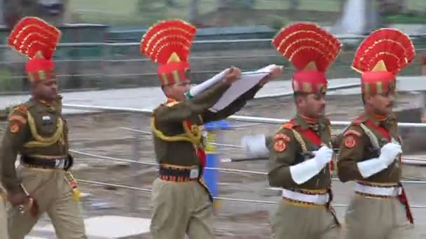 Border guards carry a flag at the military ceremony at India-Pakistan border