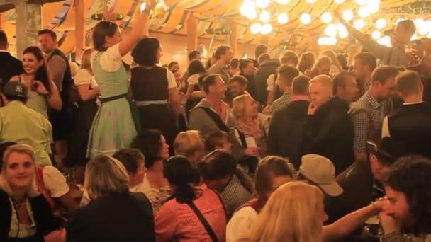 Menschen trinken Bier in einem der Zelte des Oktoberfestes in München.