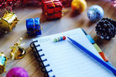 Fotografie Blank notebook with letter beads wording LIST to write down what plans to do and Christmas and New year ornaments on wooden table, selective focus and added color filter