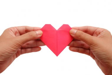 Hand holding red heart paper origami on white background for Valentine's day and love concept