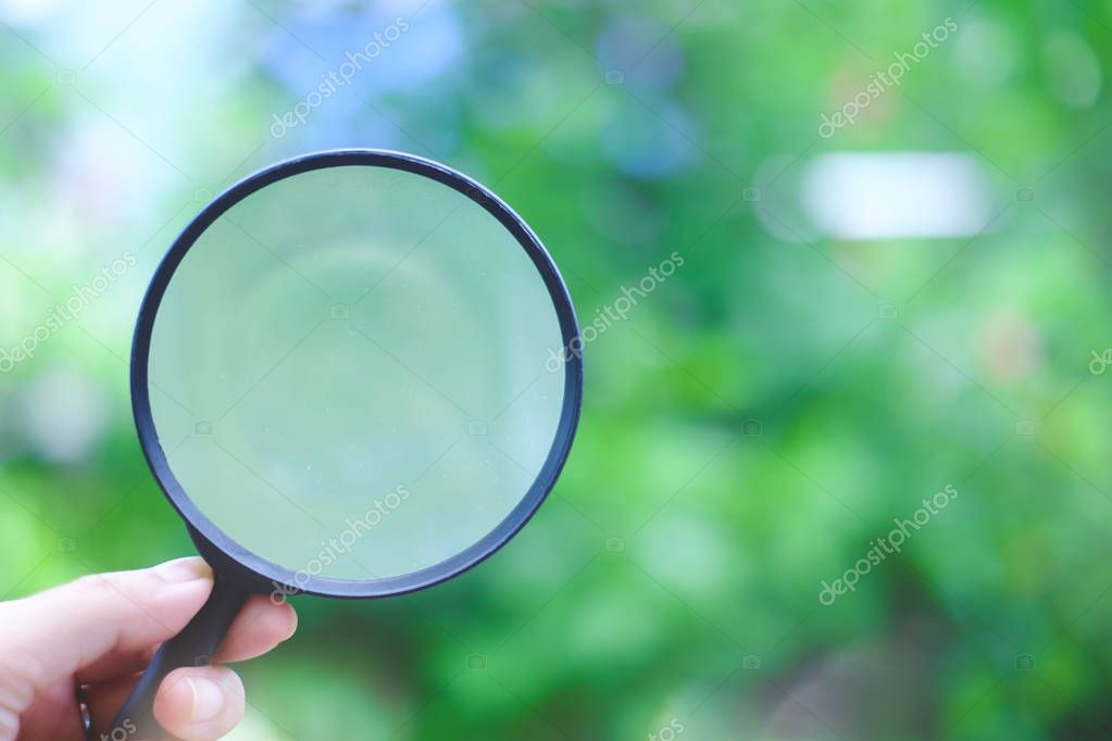 Hand holding a magnifying glass on blurred natural green backgro