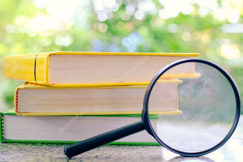 Stack of textbooks zoomed by the magnifying glass on blurred nat