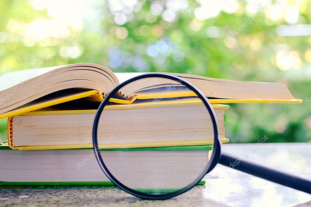 Books zoomed by the magnifying glass on blurred natural green ba
