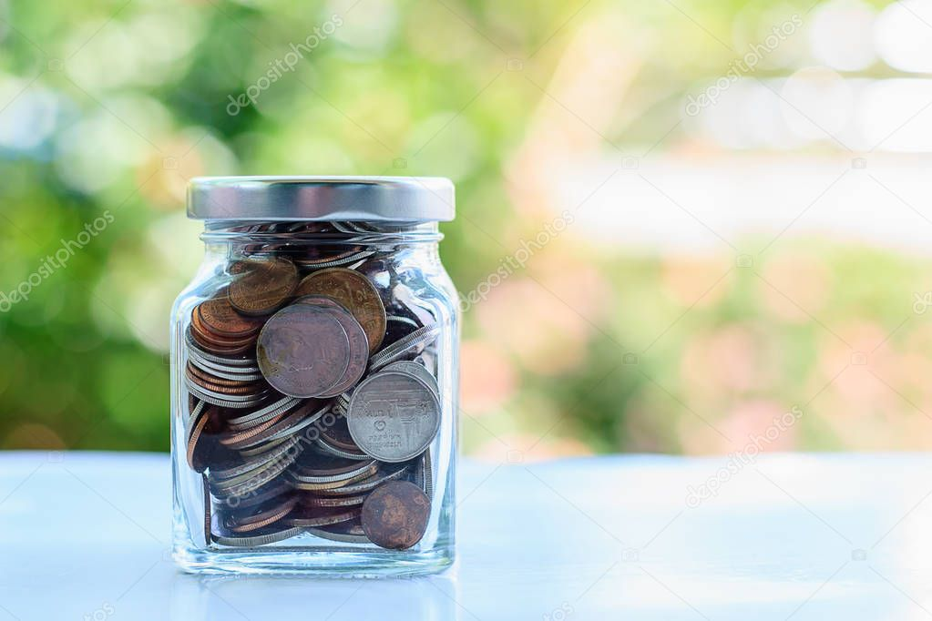 Coins in glass jar against blurred natural green background
