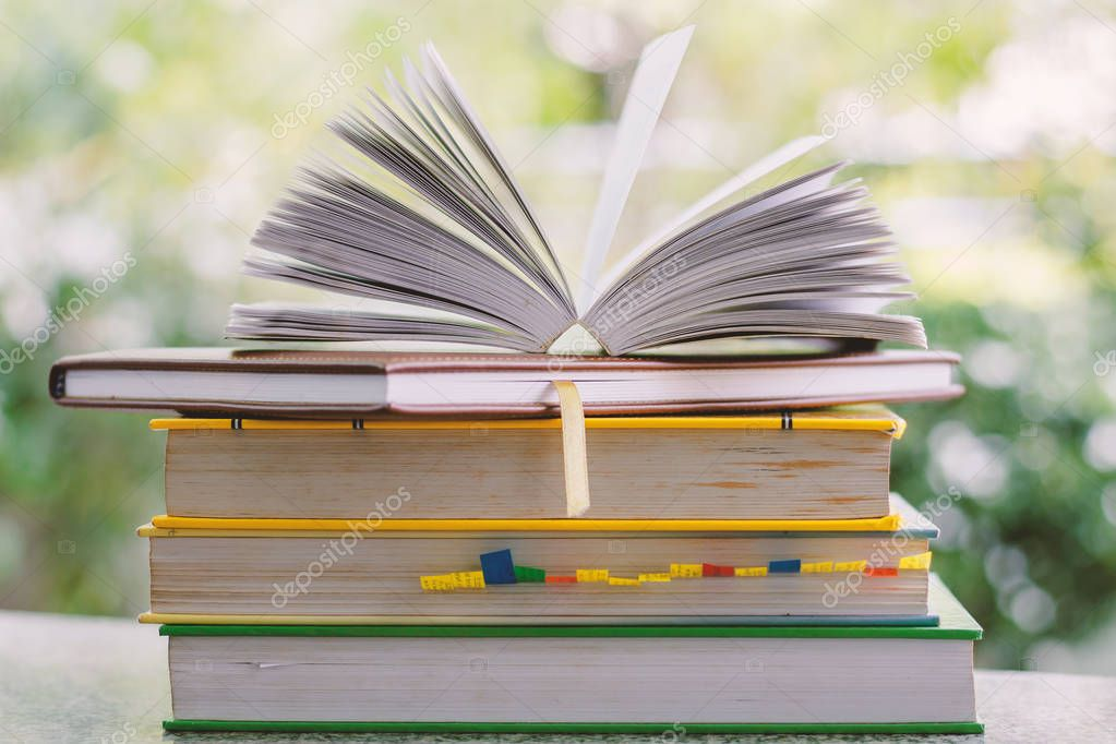 Stack of book on blurred natural green background