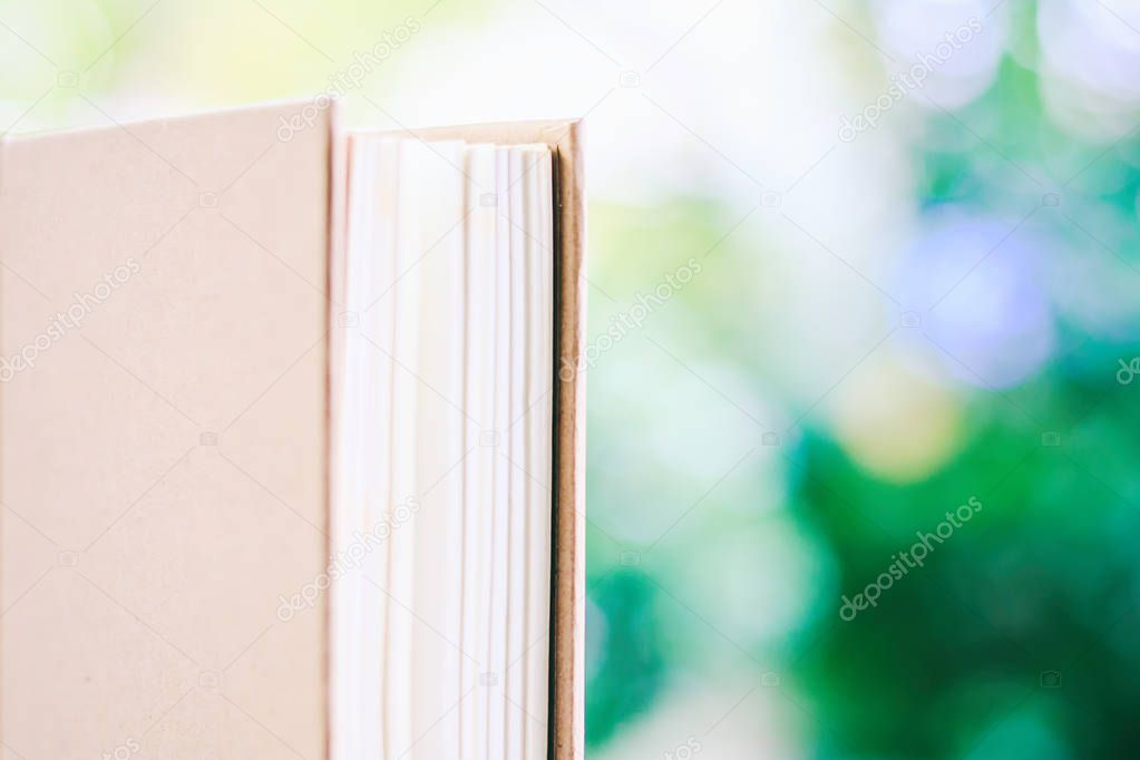 A book against blurred natural green background