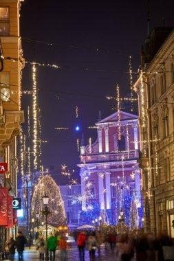 LJUBLJANA, SLOVENIA - DECEMBER 21, 2017: Advent December night with Christmas decoration lighting in Ljubljana's city center at dusk. River Ljubljanica, Triple Bridge, Preseren square and Franciscan Church of the Annunciation.