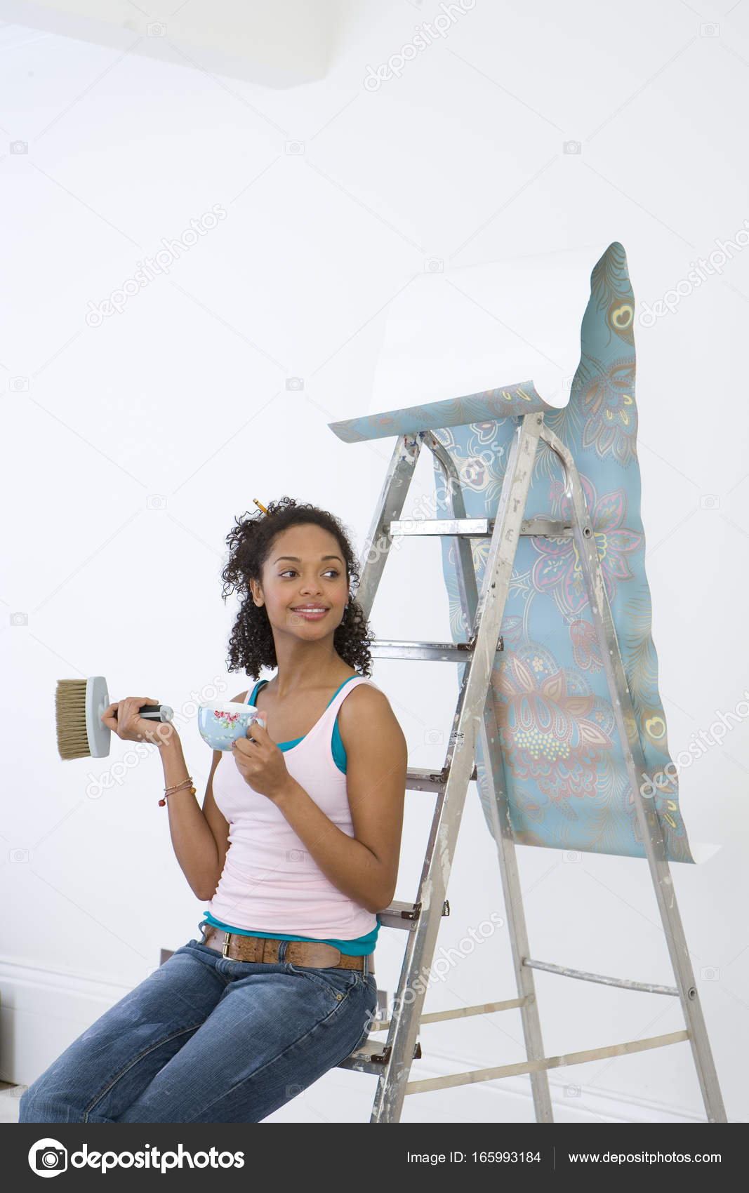 Young Woman Ladder Mug Taking Break Hanging Wallpaper Smiling Stock Photo
