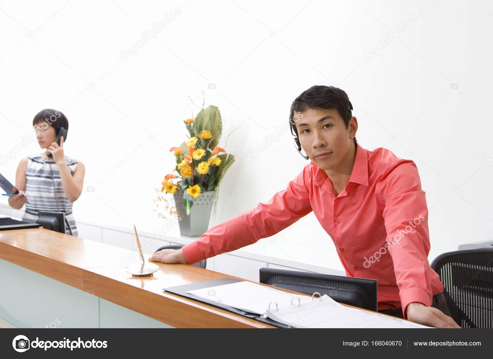 Réceptionniste m le penchant sur bureau collègue arrière plan