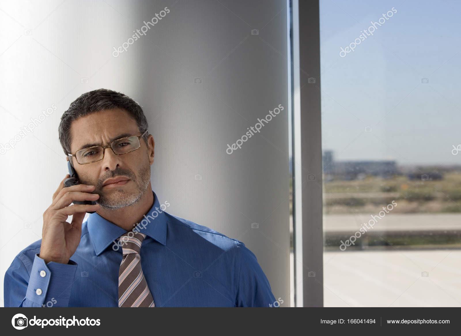 homme mature portant des lunettes aide t l phone portable c t fen tre photographie. Black Bedroom Furniture Sets. Home Design Ideas