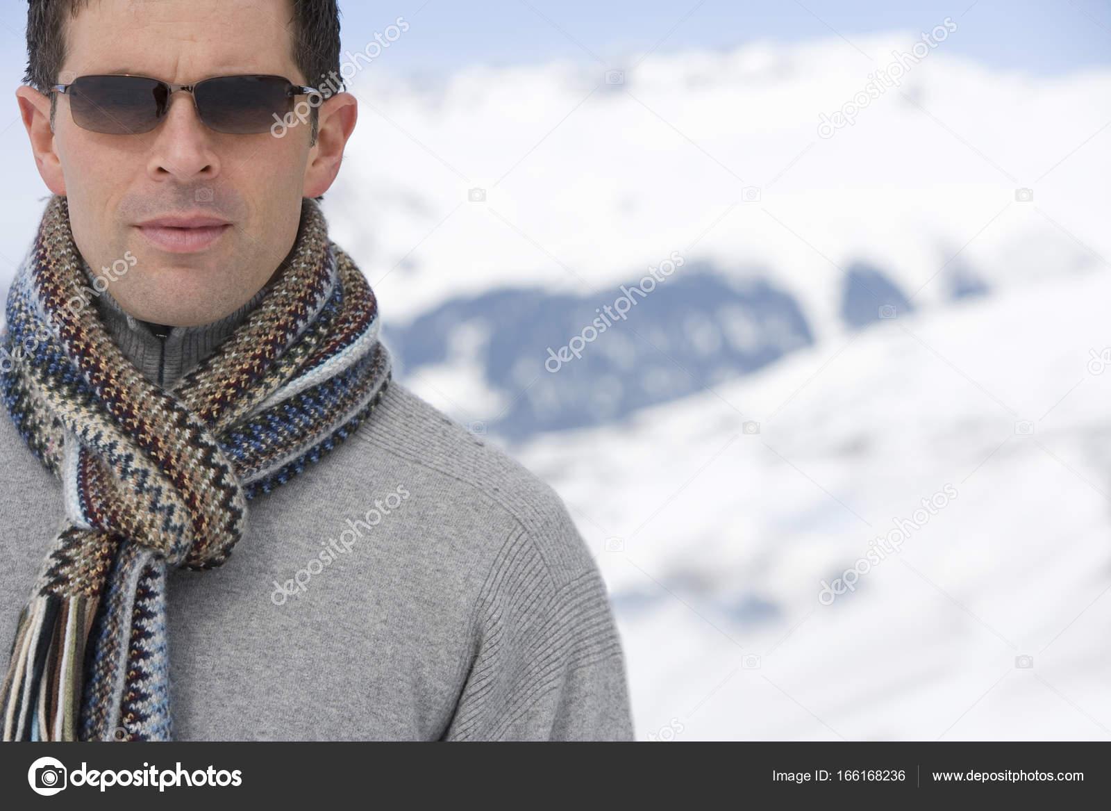 Jeune homme portant une écharpe en laine et des lunettes de soleil dans la  neige, gros plan– images de stock libres de droits 2f6e4da4ced