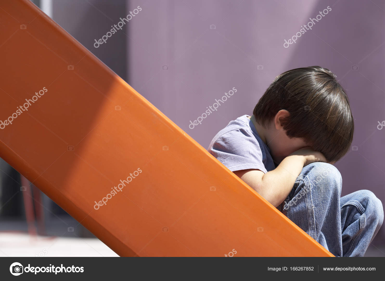 Muchacho triste sentado en la parte inferior de la diapositiva naranja en patio de la cabeza en las manos llorando perfil fotos perfil sad boy foto