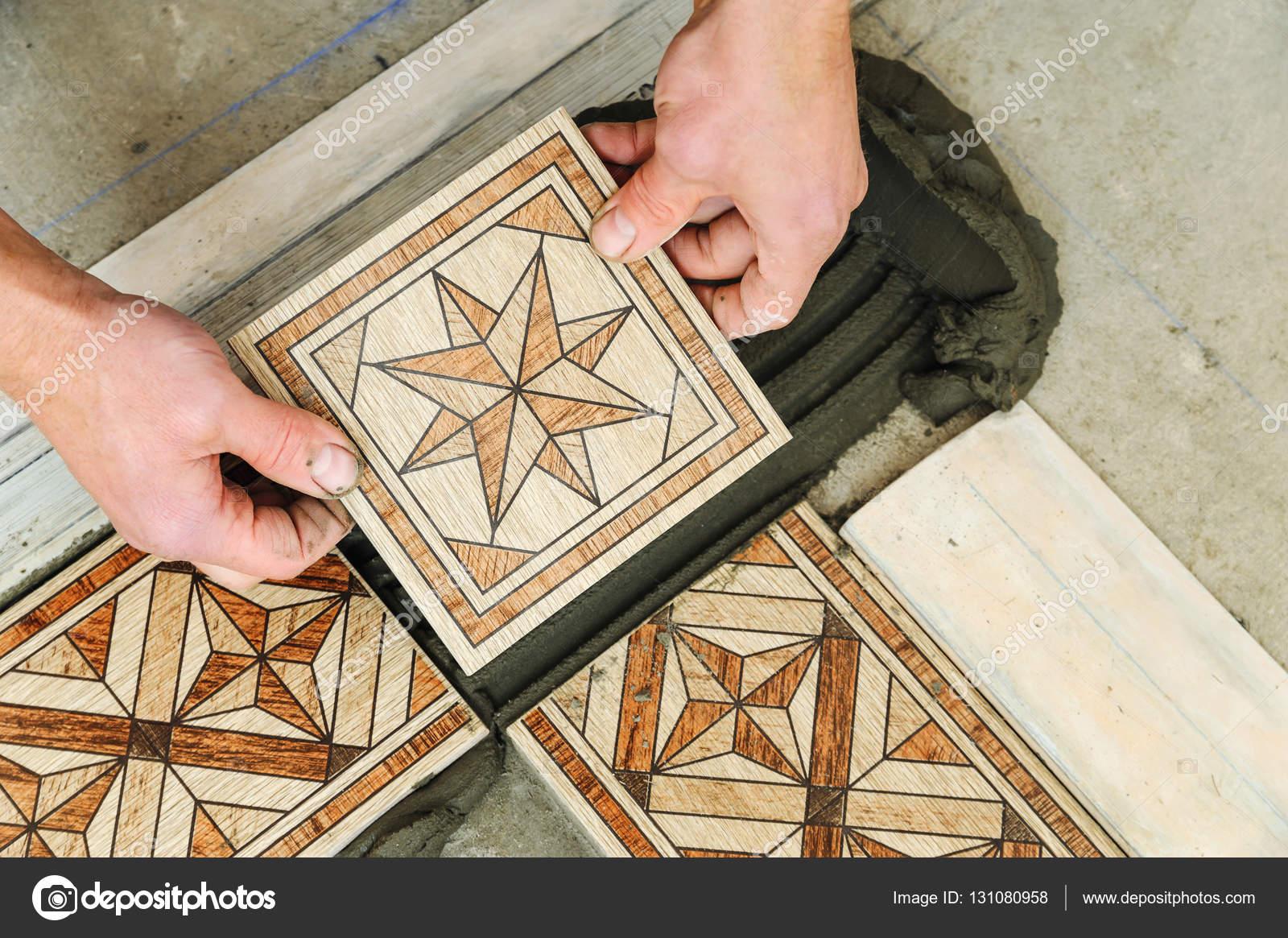 Lavoratore di mettere piastrelle sul pavimento u foto stock